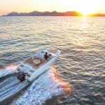 Man driving boat during sunset image
