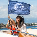 Woman and girl on boat holding freedom boat club flag
